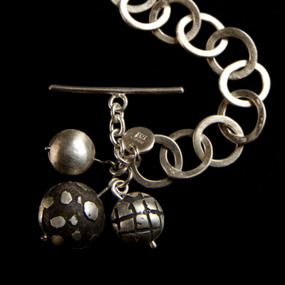 Silver link bracelet with T-bar charms.